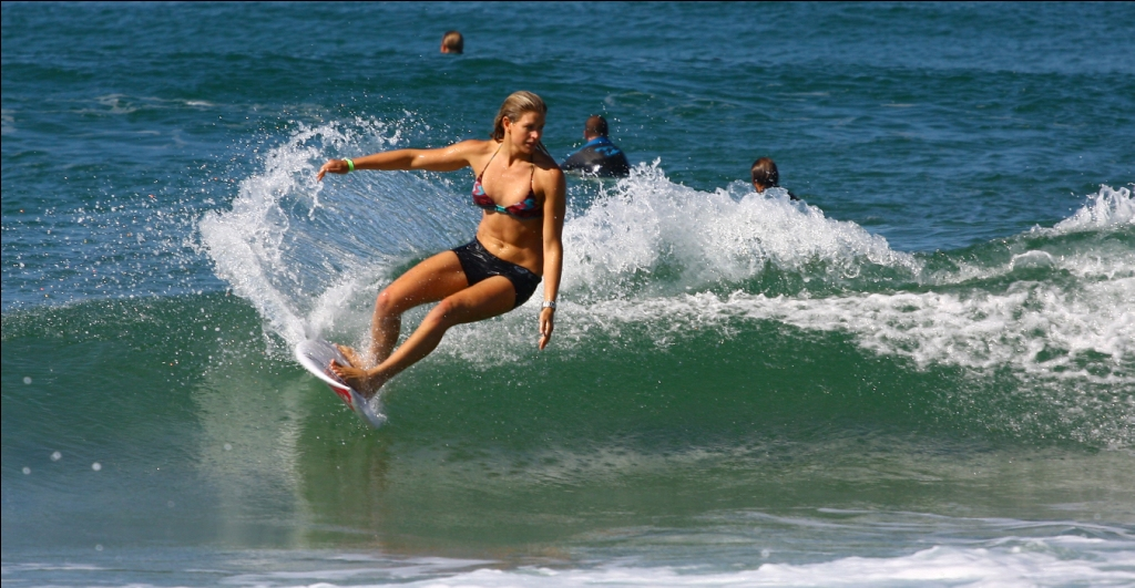 A surfer girl throws a nice cutback on a clean wave