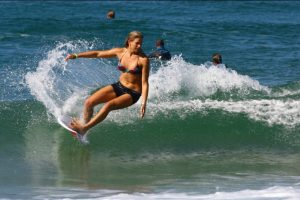 A girl in a bikini and shorts surfing small clean waves in France