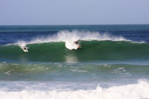 A surfer on an orange board takes off on a big green wave at Fistral Beach