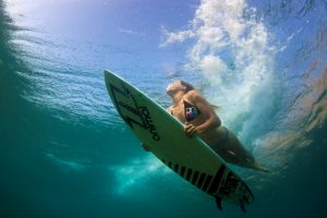 An underwater photo of a girl in a bikini duck diving the breaking surf