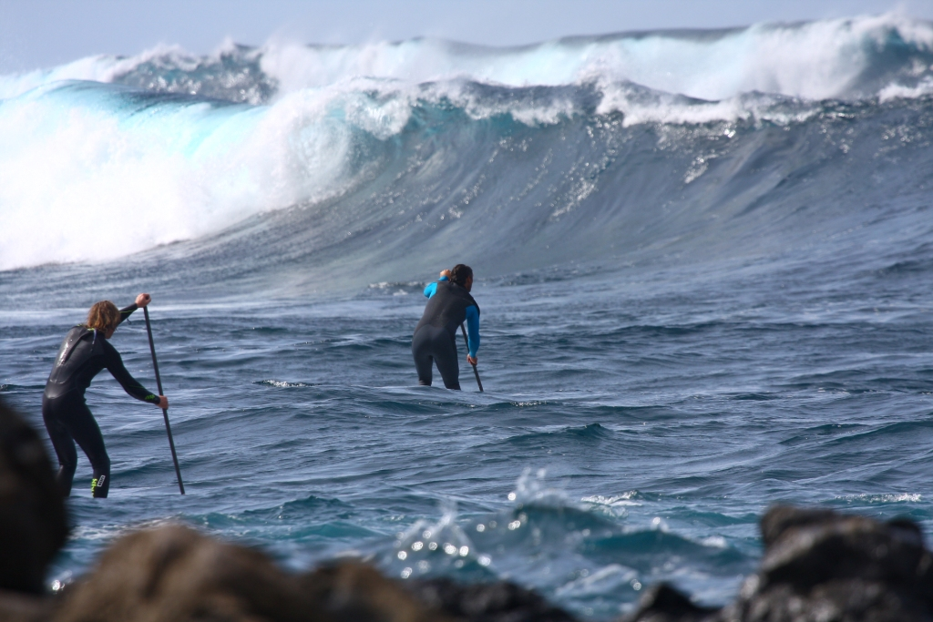 Two stand-up paddlers take the safety of a deep water channel amidst some large waves
