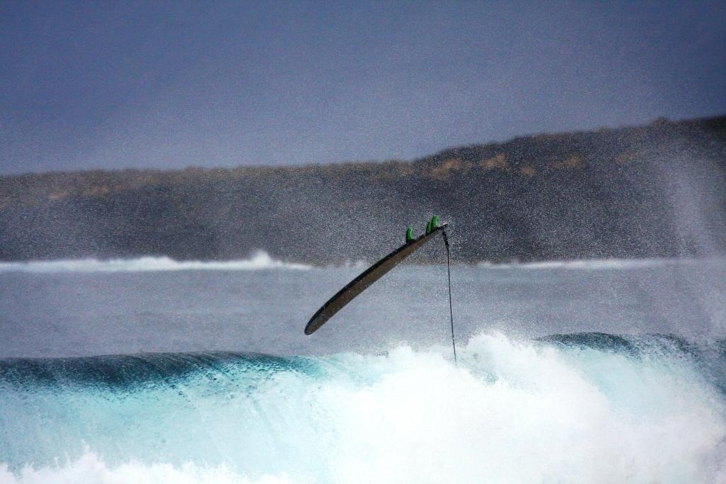 A surfer gets pummelled by a large wave and the board goes flying through the air