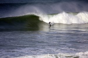 A surfer makes a bottom turn on a big right hand wave in Newquay