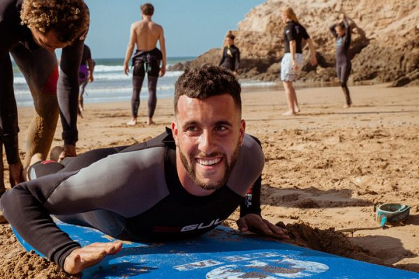 Smiling man on his board on the sand