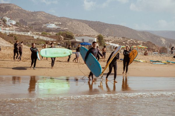 Group of people walking into the sea with surfboards