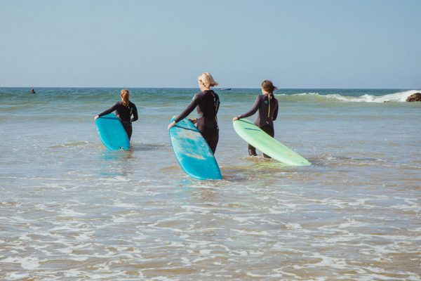 3 surf students with boards walking into sea